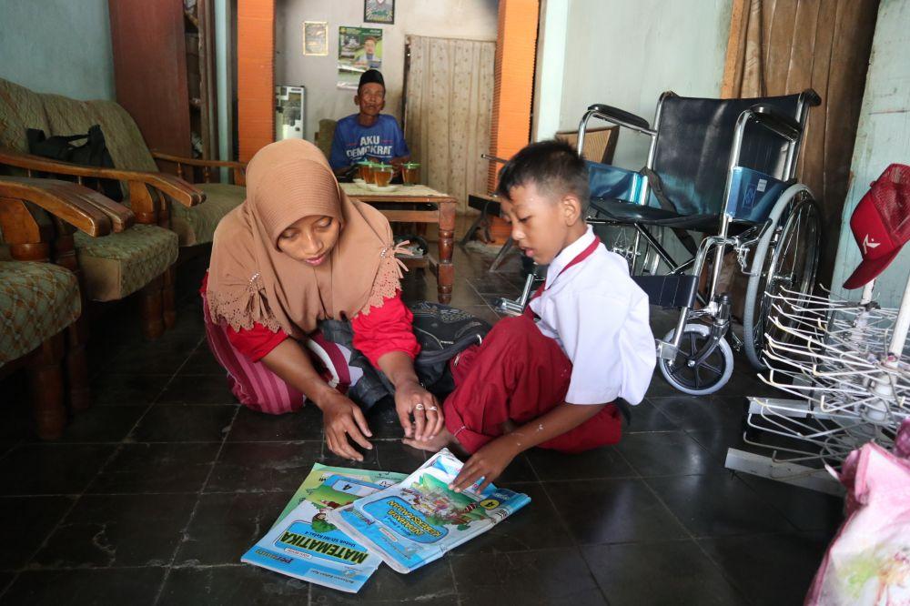 Fattan menyiapkan keperluan sekolah dibantu Tutik, ibunya