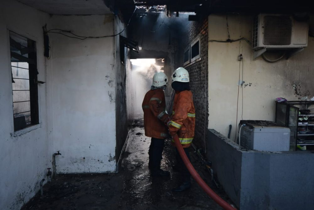 Petugas PMK melakukan pembasahan di Asrama Polisi Tandes yang terbakar