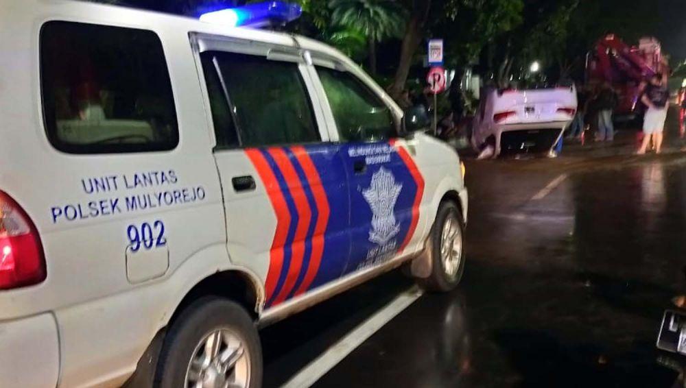 Unit Laka Satlantas Polsek Mulyorejo mengamankan TKP mobil BMW terbalik