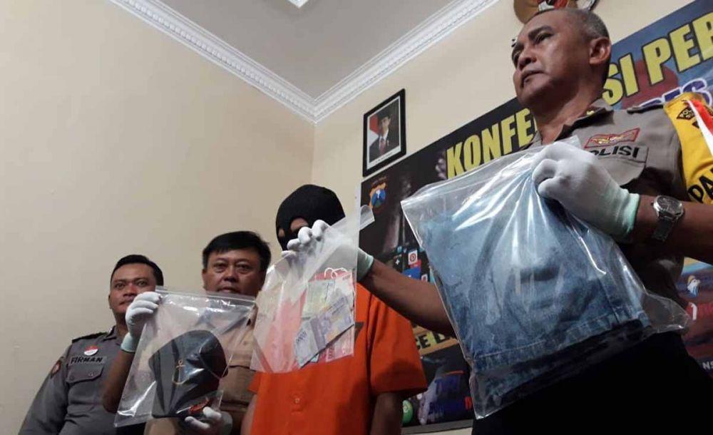 Kapolsek Tandes, Kompol Kusminto menunjukkan sang preman dan barang bukti pemerasannya