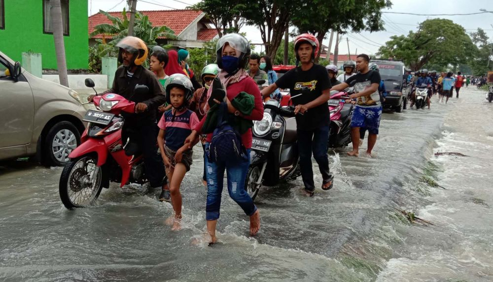 Pengendara motor menuntun motornya akibat genangan air di Jalan Raya Benjeng-Balongpanggang, Gresik