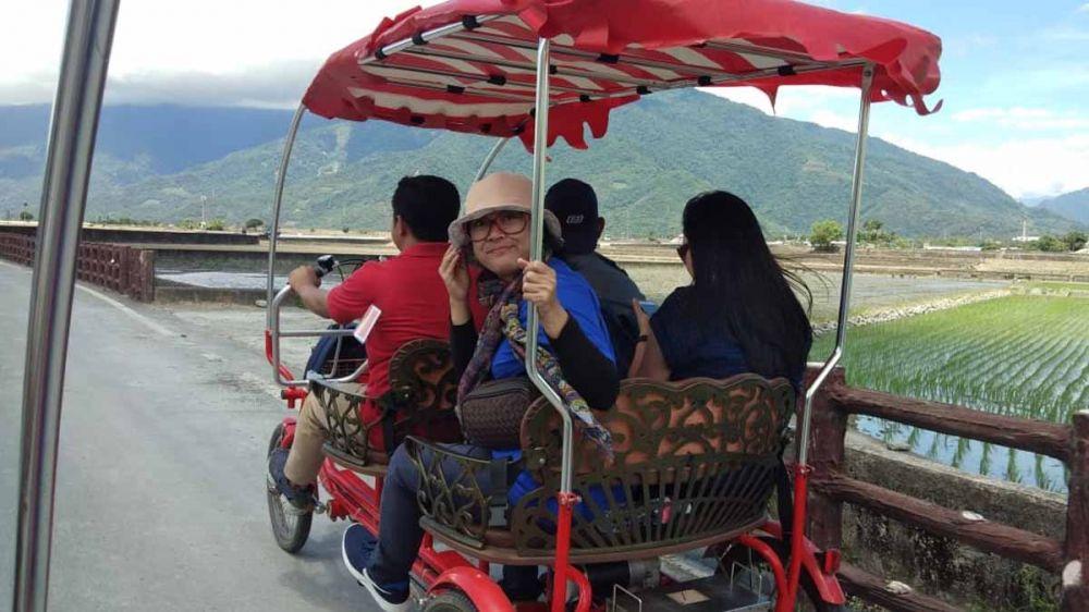 Wisatawan menikmati pemandangan alam pedesaan dengan sepeda roda empat