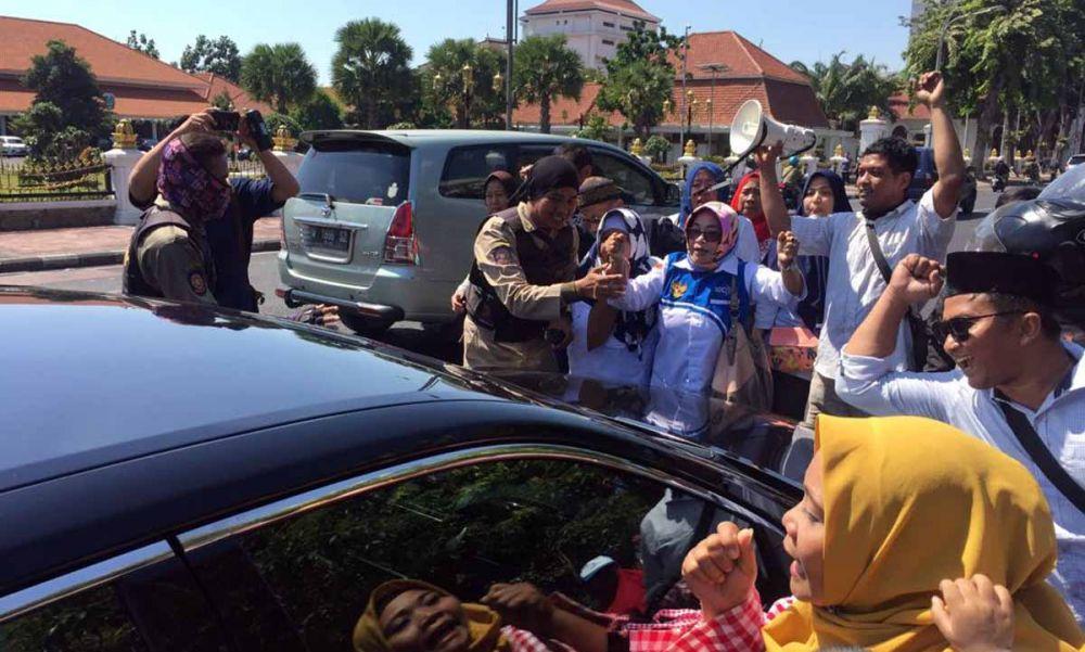 Pendemo sistem zonasi yang didominasi emak-emak menghadang mobil berplat merah di Jalan Gubernur Suryo, Surabaya