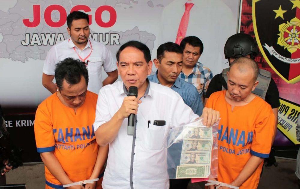 Dirreskrimum Polda Jatim Kombes Pol R Pitra Andrias Ratulangie menunjukkan dua tersangka dan uang palsu yang dibuat dan diedarkan