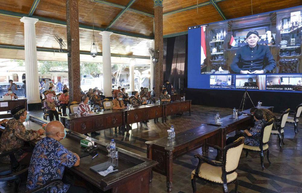 Gubernur Jawa Tengah, Ganjar  Pranowo (layar) memberikan sambutan melalui video conference dalam acara Penandatangan Perjanjian Kerjasama Pendirian Perusahaan Patungan antara PT Semen Gresik dengan 6 PT BUMDes di sekitar Pabrik Rembang