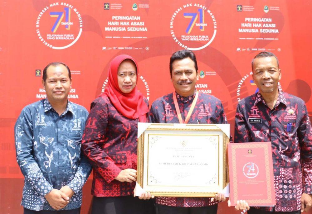 Wakil Bupati Gresik Dr. Moh. Qosim saat menunjukkan penghargaan yang diterima Gresik sebagai Kabupaten Peduli HAM