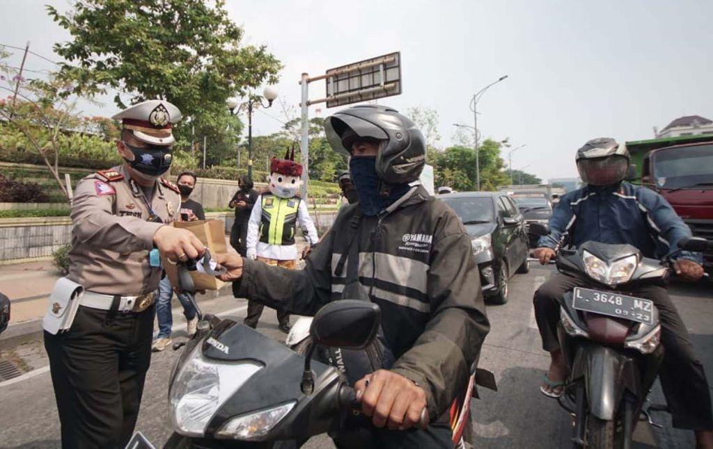 Kasatlantas Polrestabes Surabaya AKBP Teddy Chandra membagikan masker ke pengguna jalan