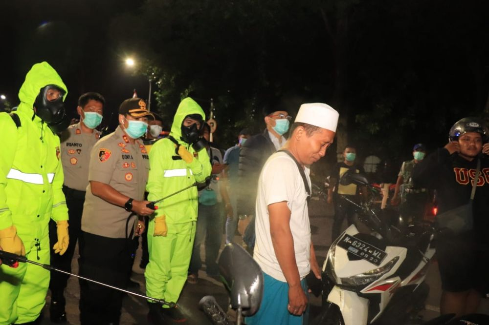 Warga Kota Pasuruan yang berkerumun disemprot disinfektan sebelum diminta bubar