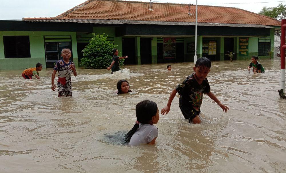 Anak-anak bermain di air banjir yang menggenangi wilayah Kecamatan Benjeng, Gresik