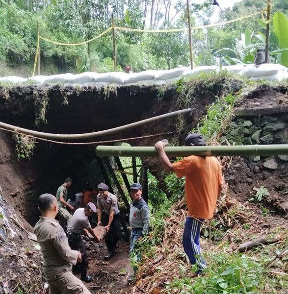 Tim gabungan memasang penyangga dari bambu serta karung berisi pasir agar jembatan yang ambrol tidak meluas