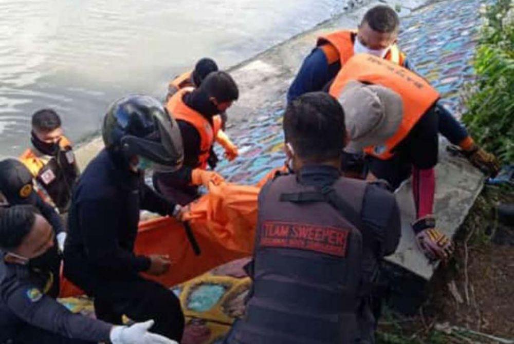 Petugas mengevakuasi jenazah pria berompi jukir dari Pintu Air Kayoon, Sungai Kalimas, Surabaya