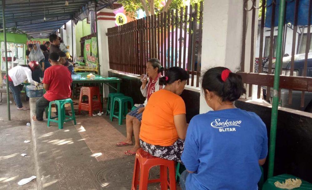 Warga menikmati nasi gratis yang dihidangkan Komunitas Hamba Allah Kota Blitar