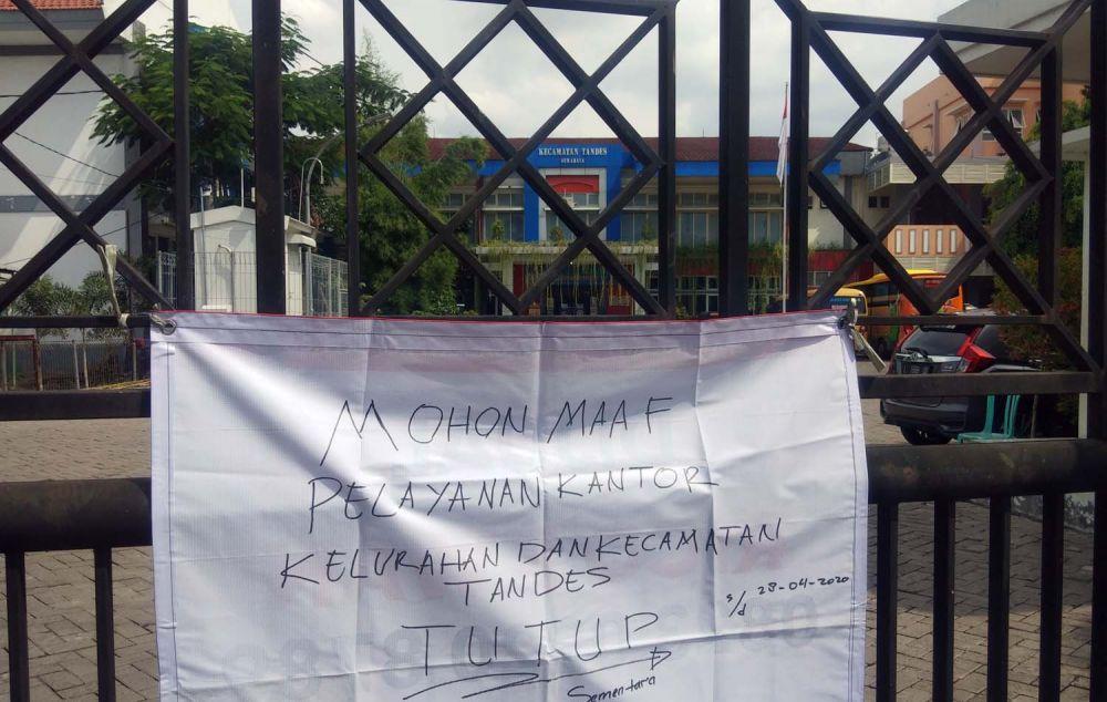 Tulisan informasi yang ditempelkan di pagar pintu masuk Kantor Kecamatan dan Kelurahan Tandes, Surabaya