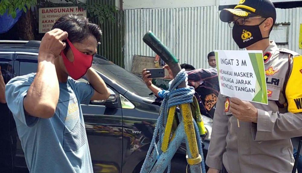 Wakapolres Pelabuhan Tanjung Perak Kompol Anggi Saputra Ibrahim membagikan masker untuk warga di Surabaya