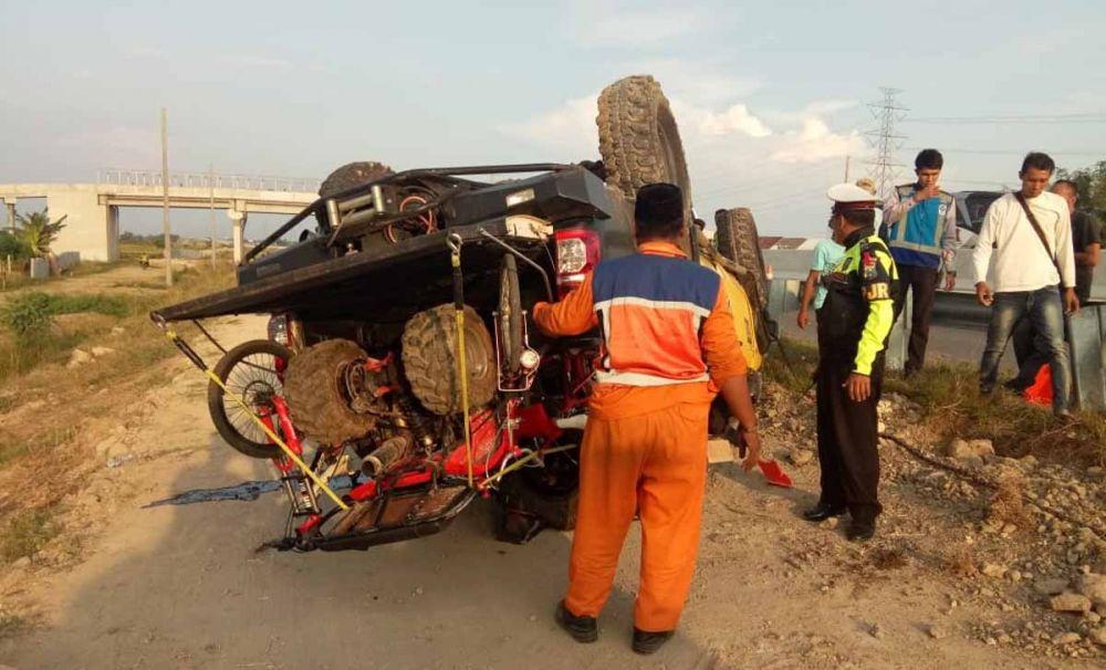 Petugas mengevakuasi Toyota Hiluk yang terbalik