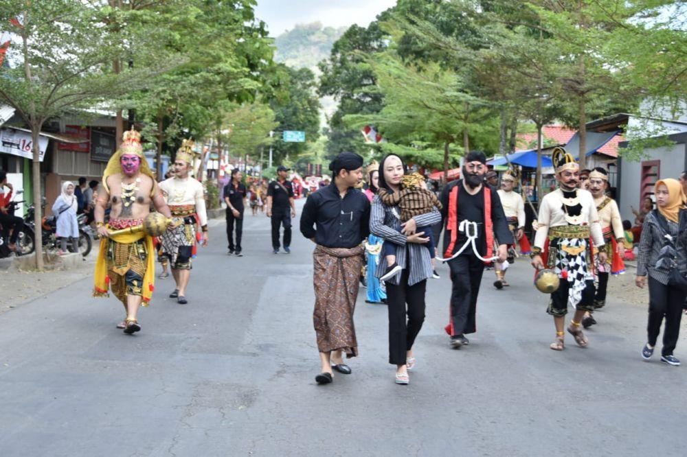 Pasangan milenial ini bergantian menggendong buah hatinya di Pawai Etnik Carnival