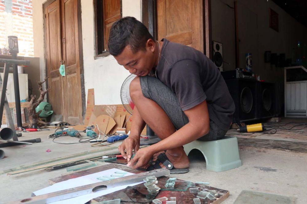 Miran, mantan TKI asal Ponorogo mulai memotong limbah kaca untuk ia jadikan miniatur menara