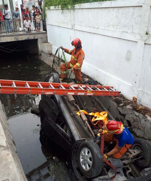 Petugas PMK Surabaya mengevakuasi mobil yang terperosok dan terbalik di selokan