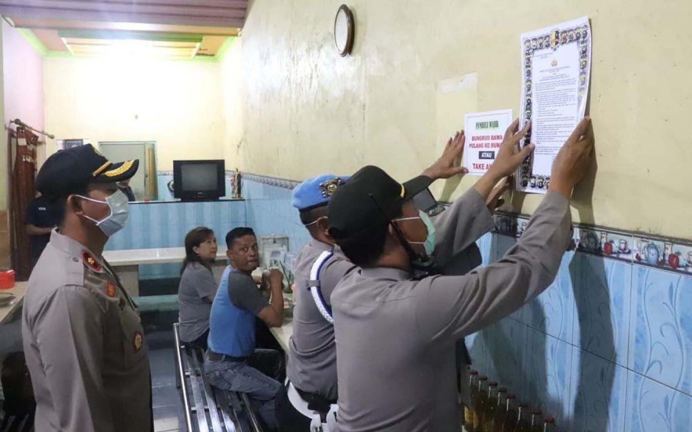 Petugas menempelkan imbauan terkait pencegahan penyebaran Virus Corona di sejumlah warung di Tulungagung