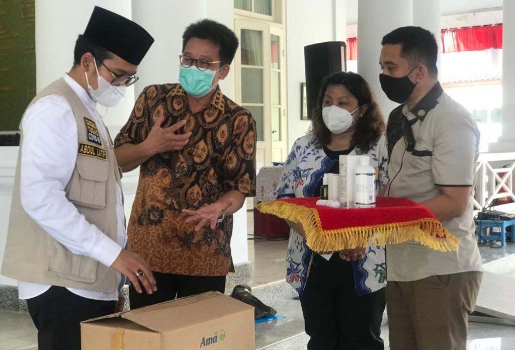 Direktur PT AMA, Recta Geson menyerahkan bantuan Pro EM1 kepada Bupati Bangkalan, Abdul Latif Imron Amin