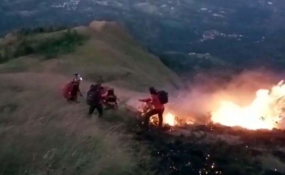 Petugas gabungan berusaha memadamkan api yang membakar 5 hektar padang savana di Gunung Penanggungan
