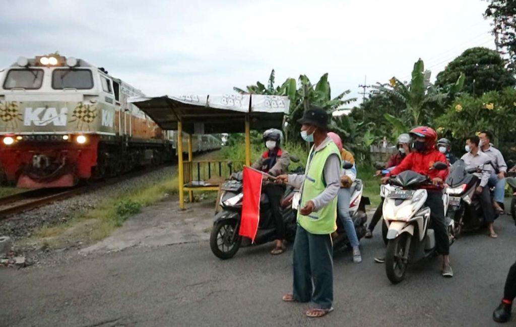 Kesi, saat menghentikan laju kendaraan yang akan melintas rel kereta api tanpa palang pintu di Surabaya