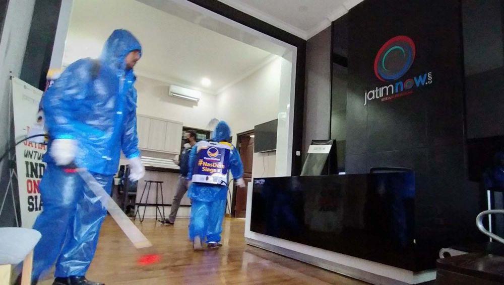 Petugas dari Partai NasDem Jatim semprotkan disinfektan di Kantor jatimnow.com Jalan Jimerto 17A, Surabaya