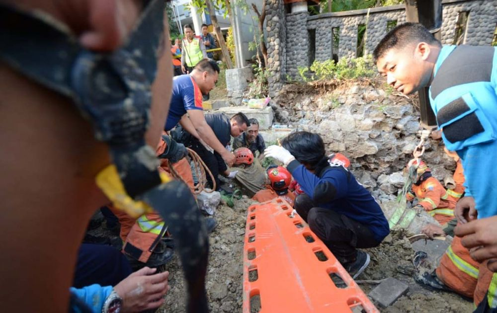 Petugas mengevakuasi dua pekerja proyek box culvert yang tertimbun dinding saluran air di Surabaya