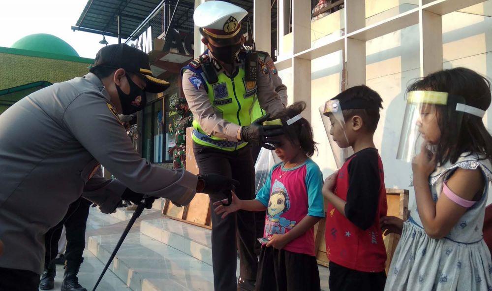 Kapolres Mojokerto AKBP Dony Alexander membagikan face shield gratis untuk anak-anak di wilayah Pacet
