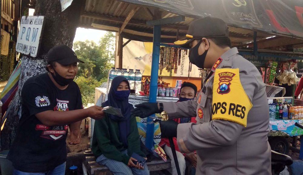 Kapolres Mojokerto AKBP Dony Alexander membagikan masker gratis untuk para pengunjung wisata Pacet