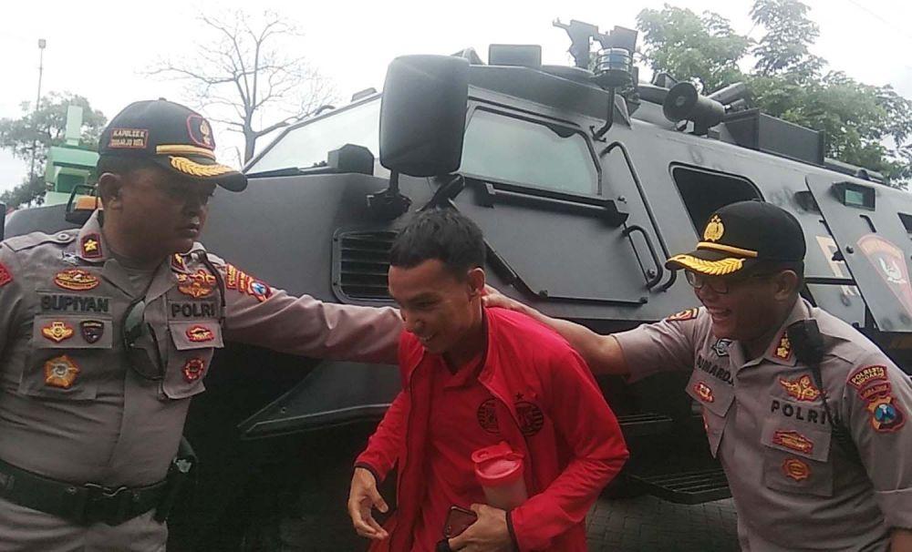 Kapolresta Sidoarjo Kombes Pol Sumardji (kanan) bercanda dengan salah satu pemain Persija yang turun dari kendaraan rantis di Stadion Gelora Delta Sidoarjo