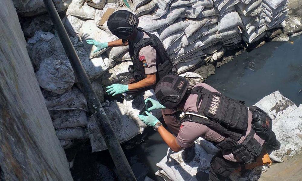 Tim Gegana Satbrimob Polda Jatim mengevakuasi benda diduga granat yang ditemukan di sungai Simokerto, Surabaya
