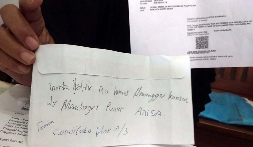 Yaidah menunjukkan tulisan tangan petugas Dispendukcapil Surabaya