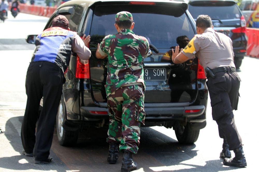 Kapolsek Tegalsari Kompol Rendy Surya Aditama mendorong mobil mogok bersama anggota Bhabinkamtibmas dan Bhabinsa di Jalan Basuki Rahmat Surabaya