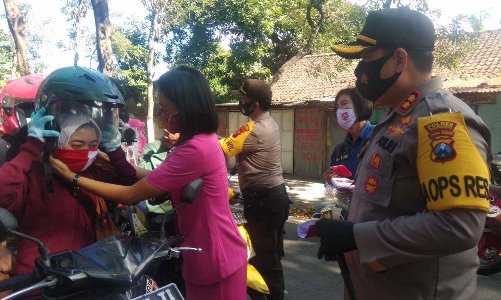 Kapolres Mojokerto AKBP Dony Alexander ikut membagikan masker merah putih
