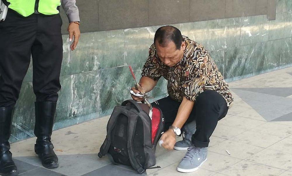 Polisi memeriksa tas milik pria misterius yang kabur dari Bank Mandiri, Jalan Kembang Jepun, Surabaya