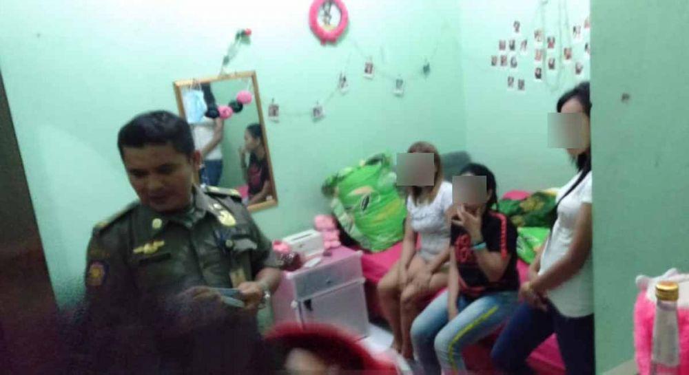 Petugas mengecek identitas penghuni salah satu kamar kos