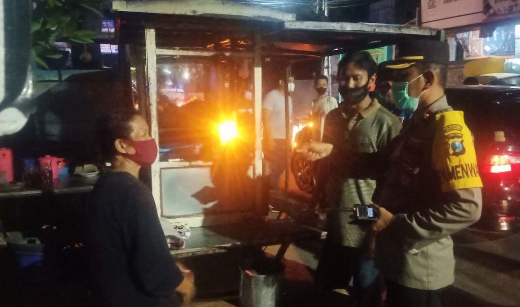 Petugas gabungan di Surabaya menindak salah satu pedagang yang melanggar PPKM Darurat