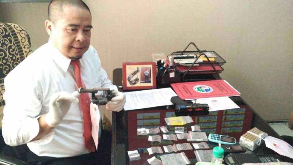 Kasat Resnarkoba Polres Pasuruan, AKP Nanang Sugiyono menunjukkan pistol sang bandar
