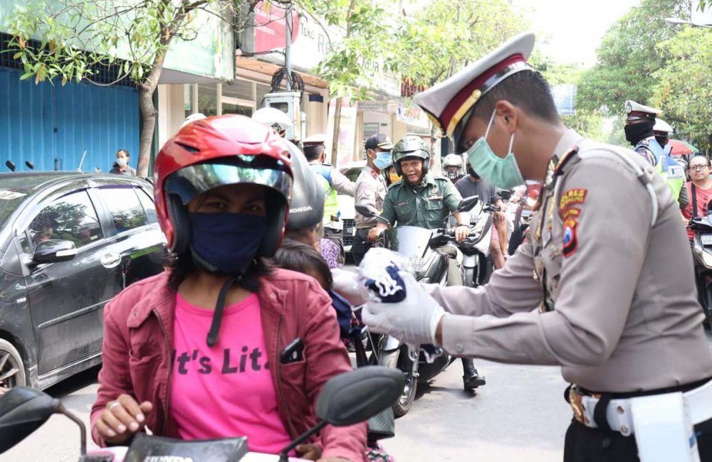 Kasatlantas Polres Tulungagung AKP Aristianto Budi Sutrisno memberikan masker gratis untuk salah satu warga