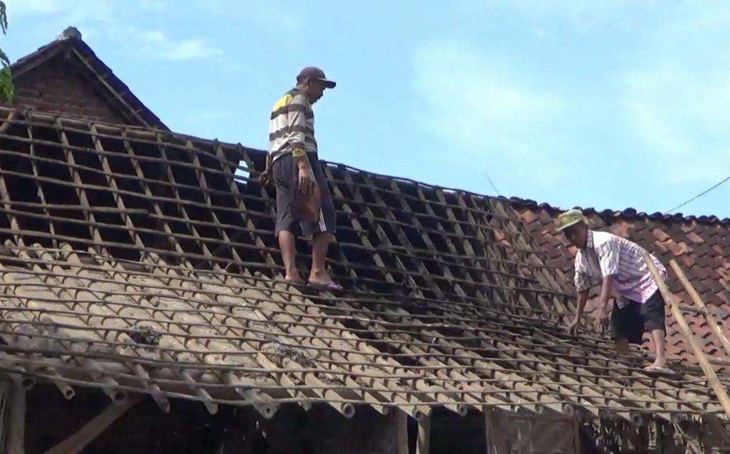 Warga di Pasuruan memperbaiki rumahnya yang rusak akibat hujan angin