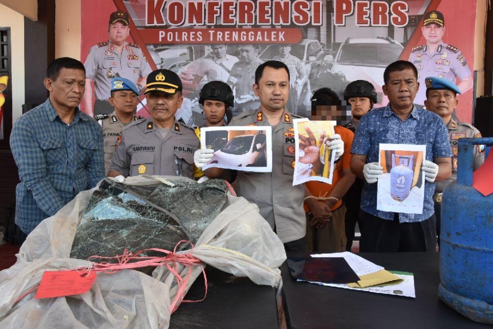 Kapolres Trenggalek AKBP Jean Calvijn Simanjuntak menunjukkan foto perusakan mobil dan penganiayaan yang dilakukan tersangka
