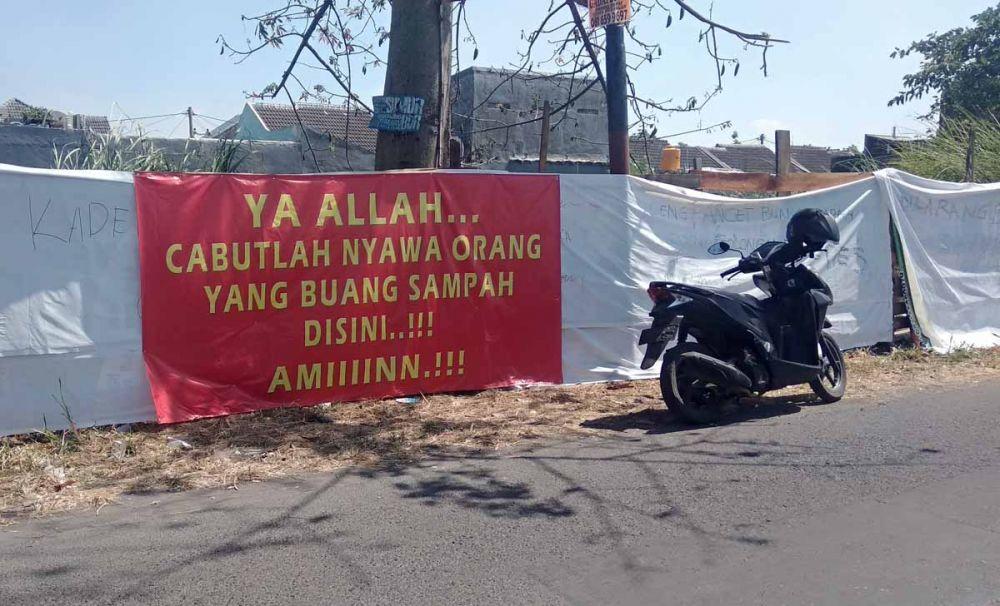 Spanduk peringatan untuk pembuang sampah terpasang di Dusun Tani Nelayan, Desa Pepe, Kecamatan Sedati, Kabupaten Sidoarjo (foto-foto: Achmad Supriyadi/jatimnow.com)