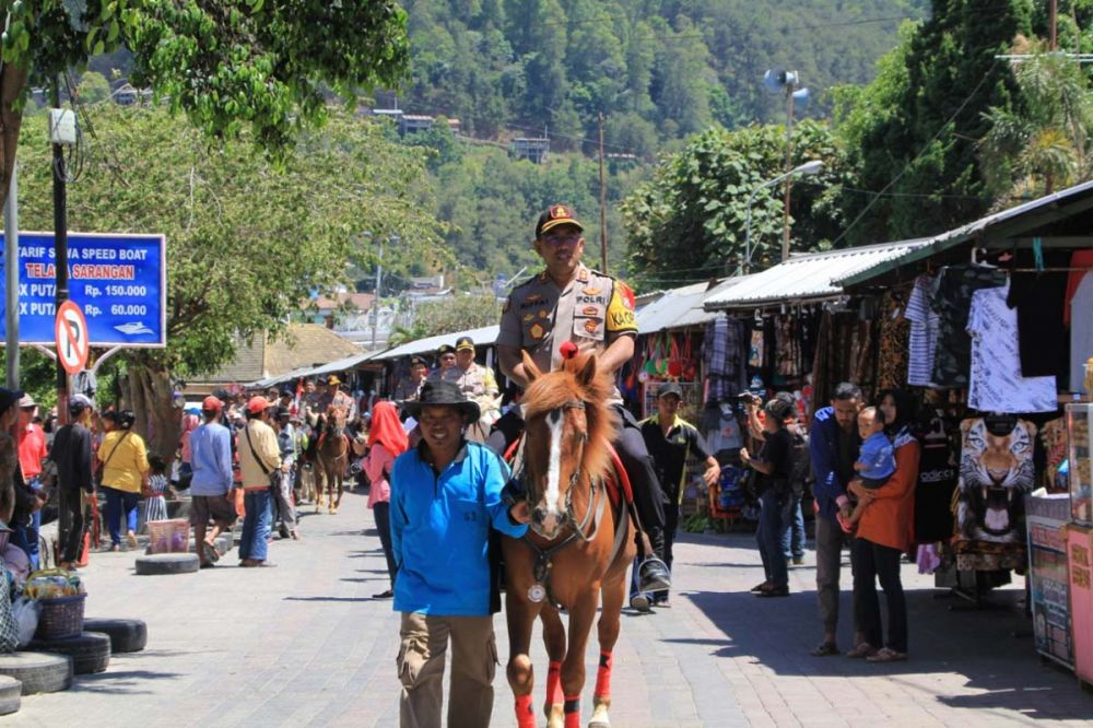 Kapolres Magetan AKBP M Rifai menunggang kuda menuju tempat syukuran di Telaga Sarangan