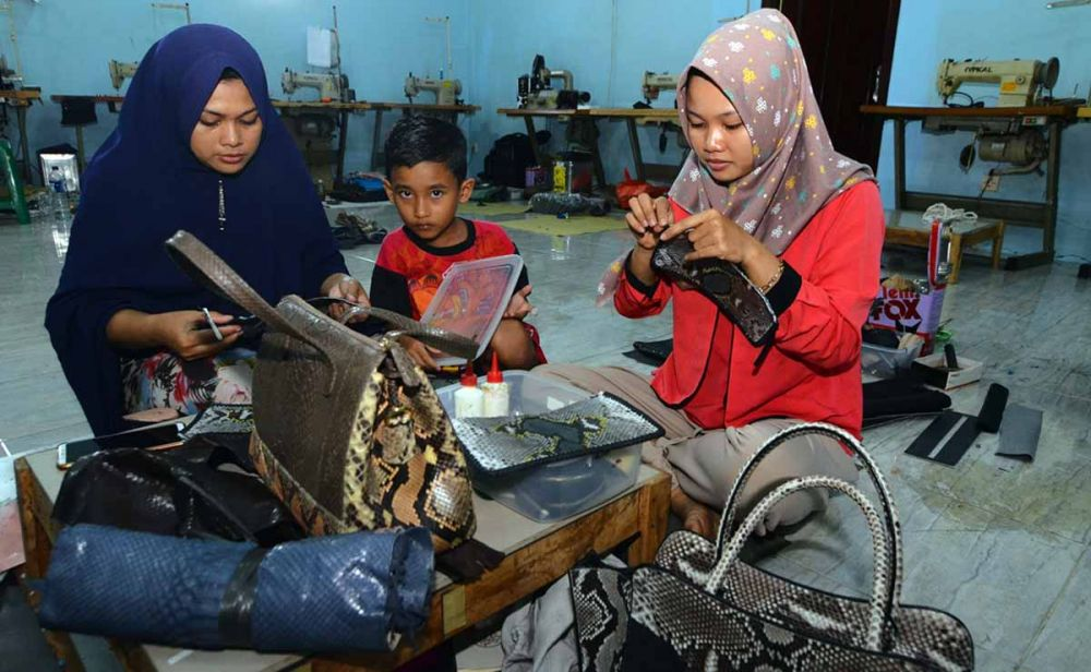 Para pekerja sedang membuat tas berbahan kulit ular di Banyuwangi