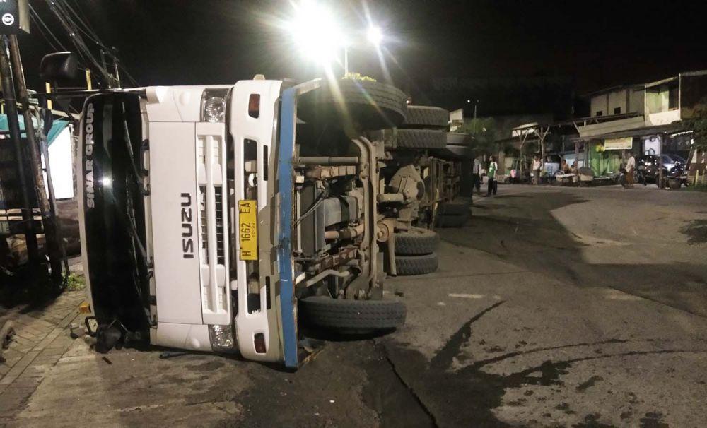 Truk trailer pengangkut kayu gelondongan terguling di Jalan Manukan Wetan, Tandes, Surabaya