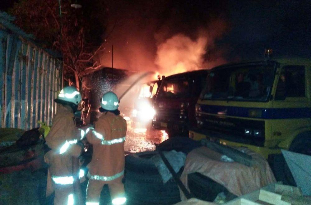 Petugas pemadam kebakaran berusaha memadamkan api yang membakar truk