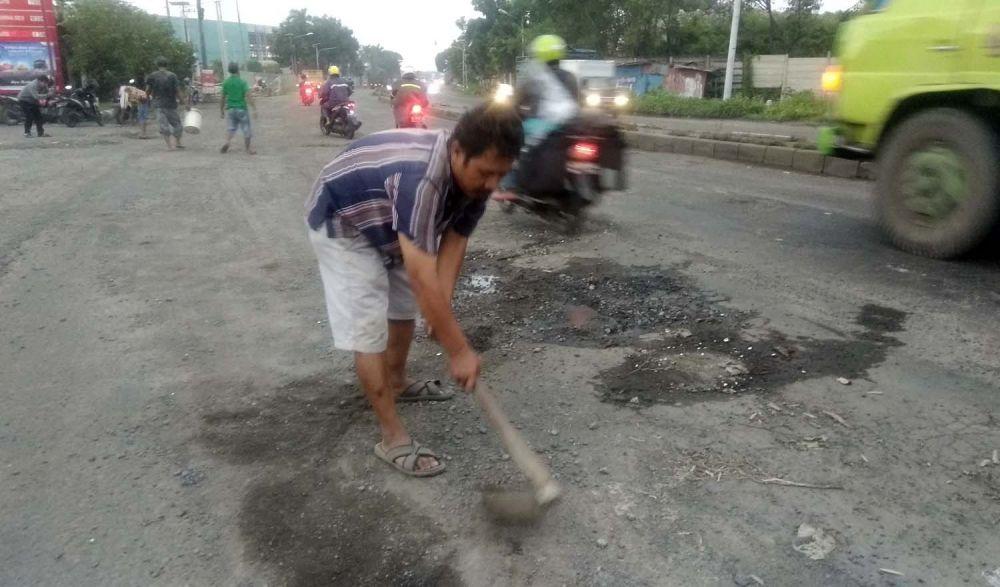 Warga menambal lubang Jalan Trans Nasional di Mojokerto