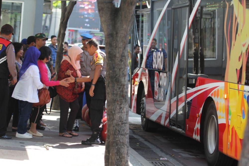 Polisi dan TNI menyapa warga yang hendak naik Bus Suroboyo di Jalan Basuki Rahmat Surabaya