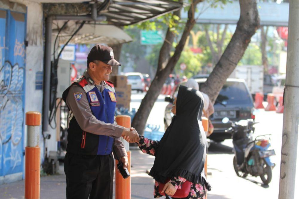 Anggota Bhabinkamtibmas Polsek Tegalsari menyapa warga di pedestrian Jalan Basuki Rahmat Surabaya